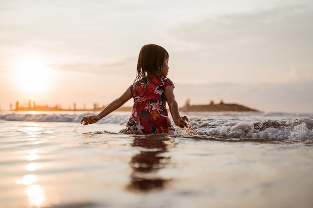 Uma menina sentada na areia na praia