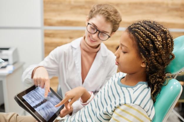 Uma menina sentada na cadeira olhando para uma imagem de raio-x de seus dentes junto com o dentista na clínica odontológica