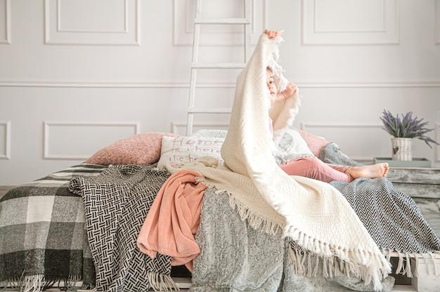 Uma menina sentada na cama com lindos cobertores do quarto.