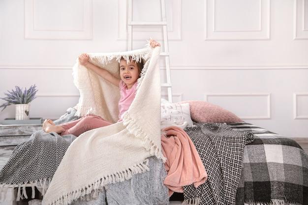 Uma menina sentada na cama com lindos cobertores, sobre um fundo claro do quarto.