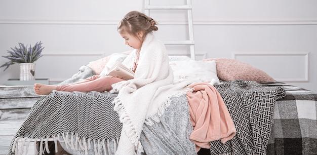 Uma menina sentada na cama e lendo um livro sobre o fundo de um lindo quarto.