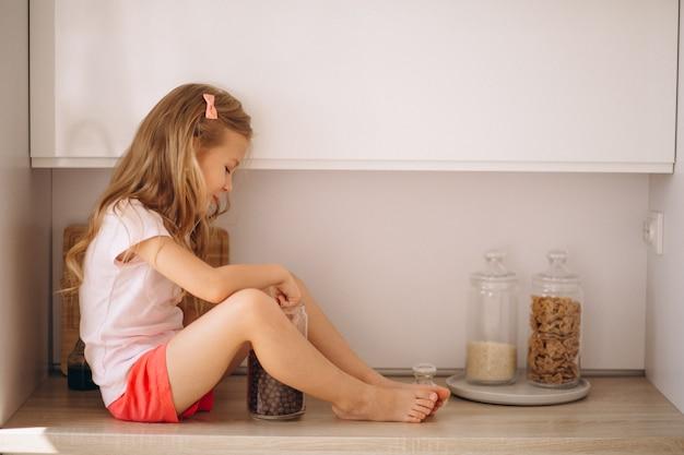 Uma menina sentada na cozinha