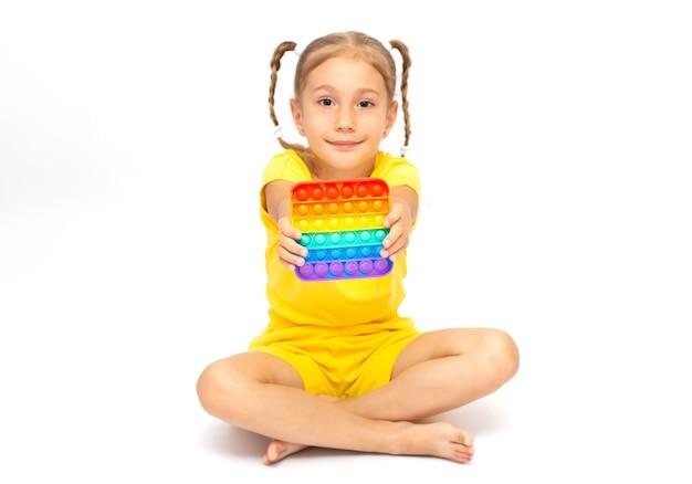 Uma menina sentada na superfície branca brincando com o novo brinquedo poppit fidget, popular entre as crianças, ajuda-as a se concentrarem