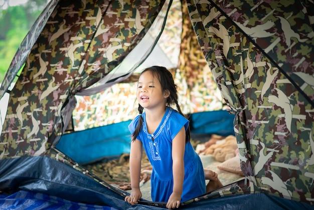 Uma menina sentada na tenda, indo acampar