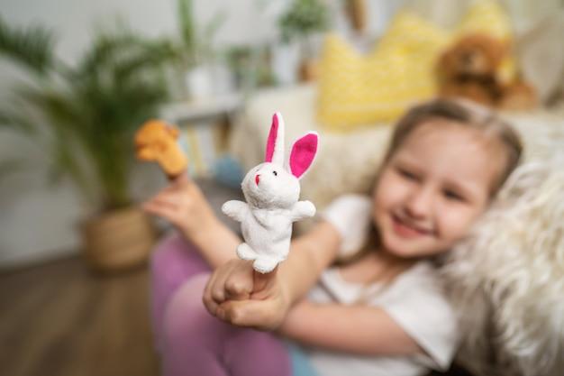 Uma menina sentada no chão, apoiando-se na diversão de sofand brincando com brinquedos de dedo