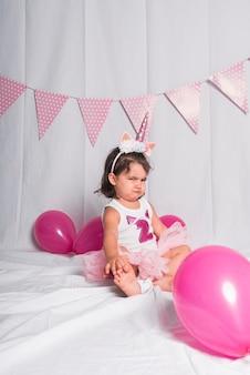 Uma menina sentada no chão com uma coroa de chifre de unicórnio fazendo gestos.