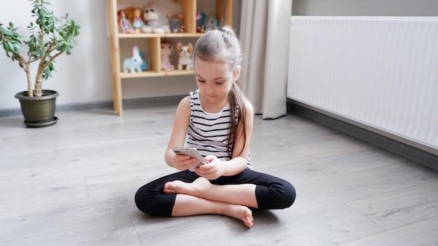 Uma menina sentada no chão de madeira com um telefone, assistindo um desenho animado ou fazendo uma chamada de vídeo