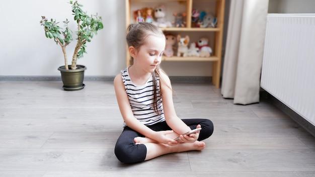 Uma menina sentada no chão de madeira com um telefone