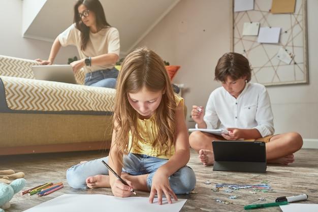 Uma menina sentada no chão desenhando enquanto o irmão dela faz o dever de casa on-line no digital