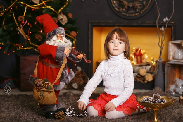 Uma menina sentada no chão em belas decorações de natal. menina brincando com um brinquedo de papai noel. preparação de ano novo.