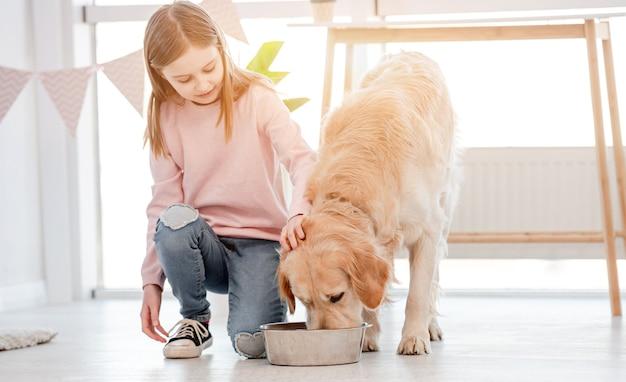 Uma menina sentada no chão olhando como um cachorro retriever dourado comendo