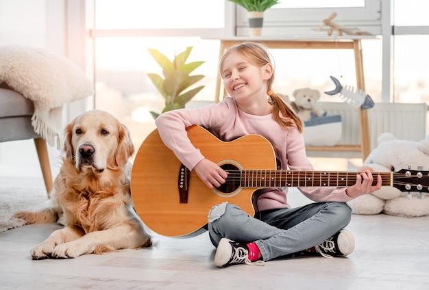 Uma menina sentada no chão tocando violão com o cachorro golden retriever deitado ao lado dela