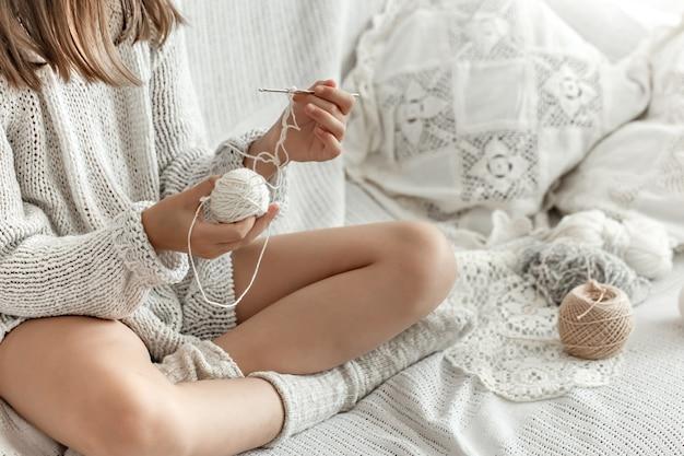 Uma menina sentada no sofá com fios, conceito de lazer em casa, crochê.