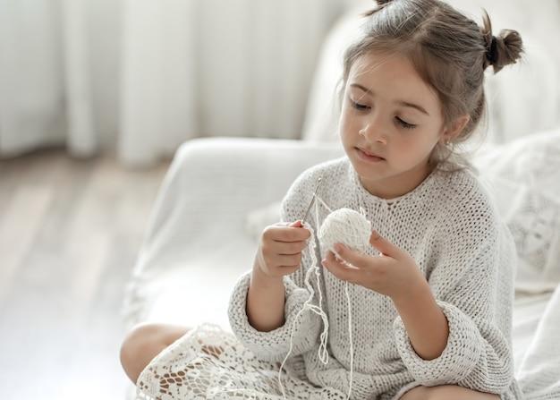 Uma menina sentada no sofá e aprendendo a tricotar, o conceito de lazer em casa.