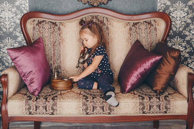 Uma menina sentada no sofá falando em um telefone antigo