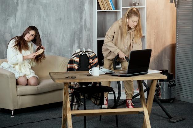 Uma menina sentada no sofá penteia o cabelo, sua amiga limpa a sala com um aspirador de pó