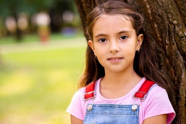Uma menina sentada perto de uma árvore, olhando para a câmera