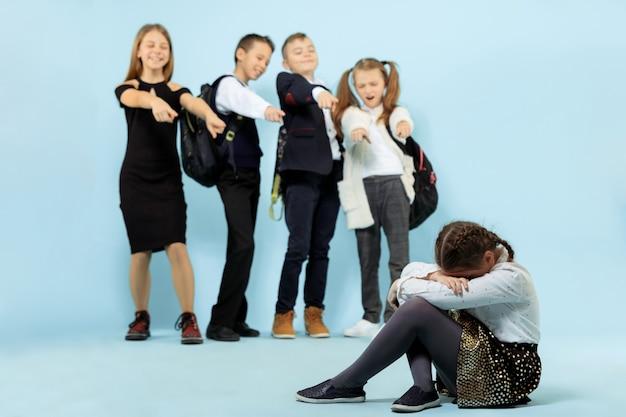 Uma menina sentada sozinha no chão sofrendo um ato de bullying enquanto as crianças zombavam
