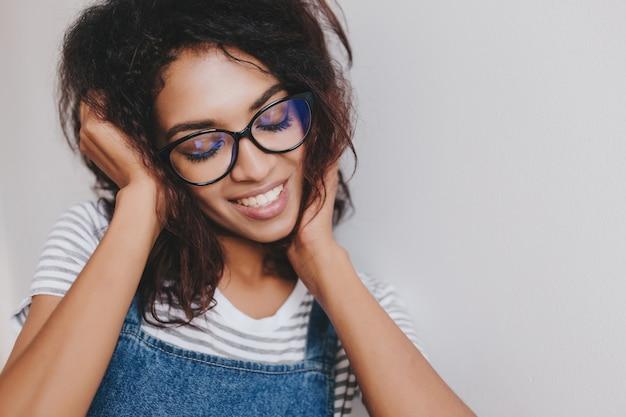 Uma menina sonhadora em óculos elegantes posando com os olhos fechados e um sorriso incrível na parede branca