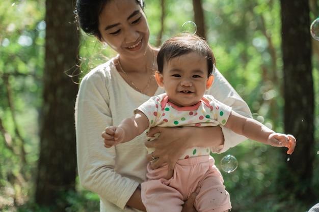 Uma menina sorri enquanto é abraçada pela mãe enquanto brinca