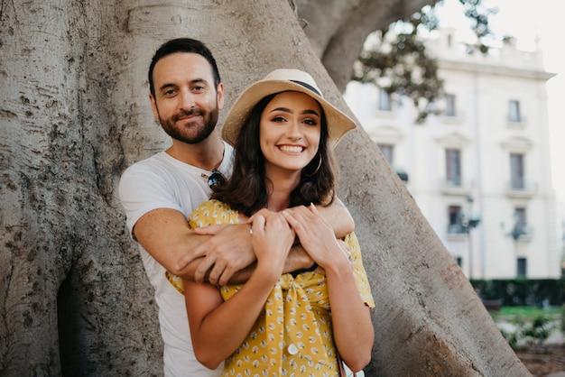 Uma menina sorridente com um chapéu e um vestido amarelo e seu namorado feliz com barba estão abraçando sob um velho ficus macrophylla valenciano