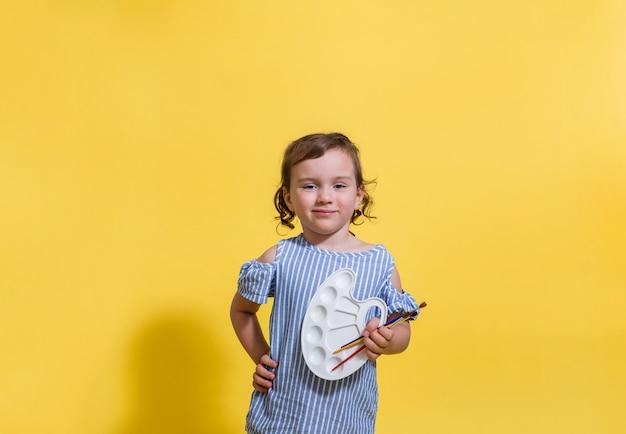 Uma menina sorridente detém uma paleta de tinta e pincéis em um fundo amarelo com espaço para texto.