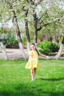Uma menina sorridente e sorridente em um vestido amarelo circula em volta de si mesma no gramado no quintal de um vi ...