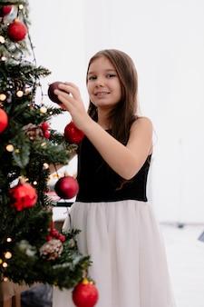 Uma menina sorridente em casa na época do natal, decorando a árvore de natal na sala de estar, segurando uma bugiganga de natal