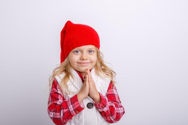 Uma menina sorridente em um chapéu de papai noel cruzou os braços na frente dela, completamente isolado em um fundo branco