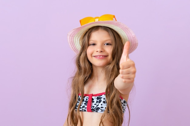 Uma menina sorridente em um maiô em um fundo isolado dá um polegar para cima.