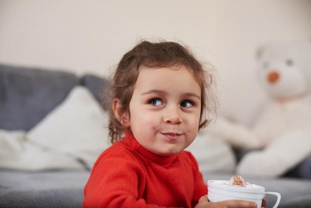 Uma menina sorridente se sente feliz enquanto bebe um chocolate quente com marshmellows
