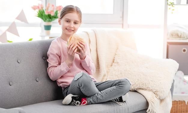 Uma menina sorridente, sentada no sofá em casa, segurando um hambúrguer nas mãos