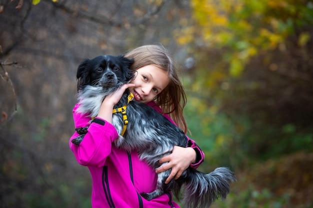 Uma menina sorridente tem um cachorro pequeno nos braços. caminhar no parque.
