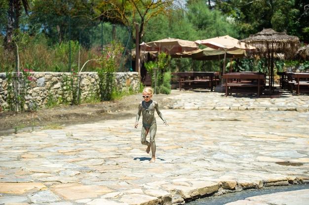 Uma menina suja corre pela rua perto de fontes curativas na turquia
