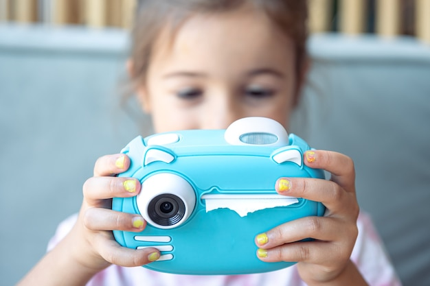 Uma menina tem nas mãos uma câmera digital de brinquedo azul para crianças para impressão instantânea de fotos.