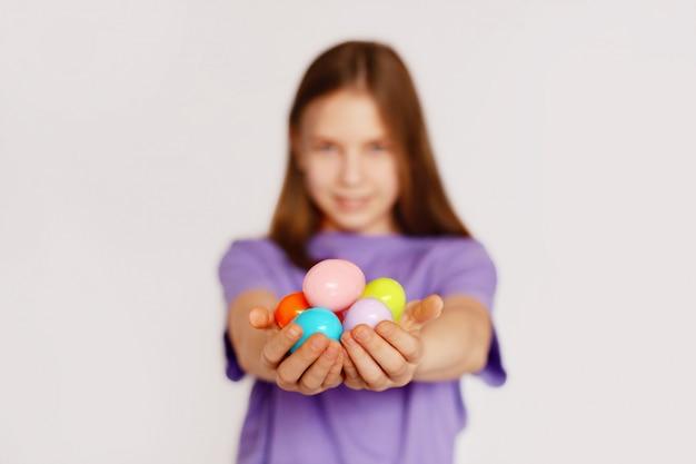 Uma menina tem ovos de páscoa coloridos nas mãos
