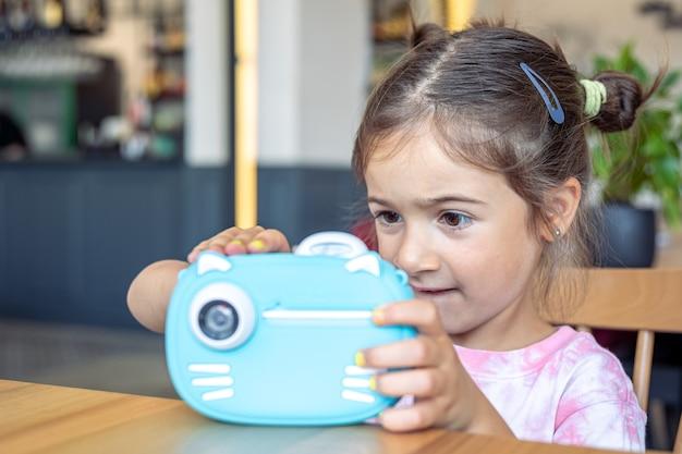 Uma menina tira uma foto com uma câmera para impressão instantânea.