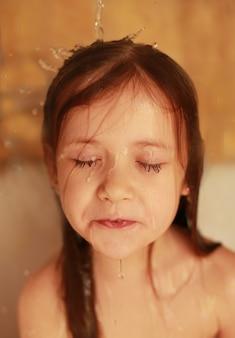 Uma menina toma banho a água corre pelo cabelo os olhos da menina estão fechados