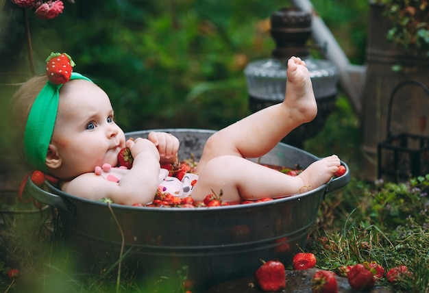 Uma menina toma banho em uma bacia com morangos no jardim.