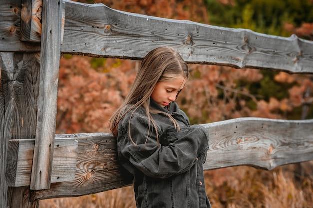 Uma menina triste envolta em uma jaqueta jeans enorme perto de uma cerca de madeira