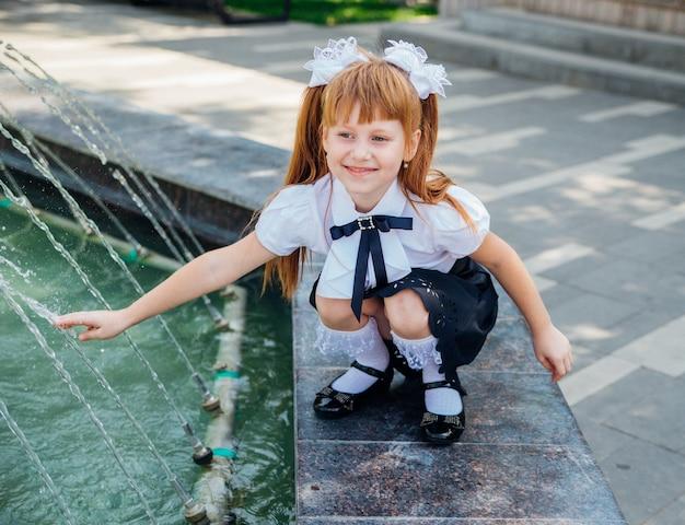 Uma menina, uma estudante do ensino fundamental, está brincando alegremente perto da fonte.