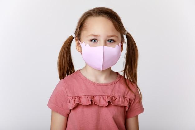 Uma menina, uma máscara de material rosa contra vírus e bactérias