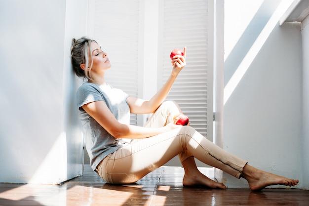 Uma menina, uma mulher com roupas brilhantes, sentada no chão, lindas mãos, maçãs, sombras da janela, equilíbrio e poder