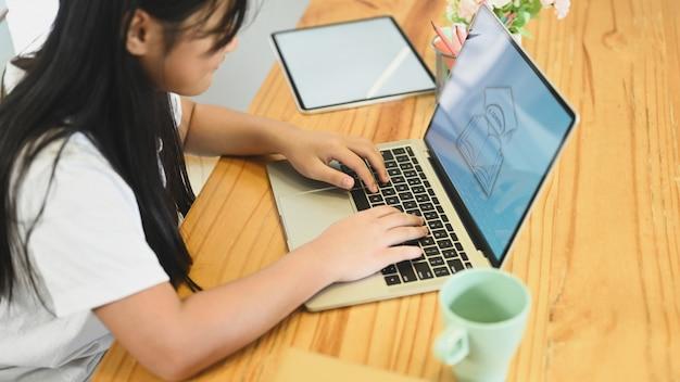 Uma menina usa um computador portátil em uma mesa de trabalho de madeira. estudando em casa, o conceito de e-learning.