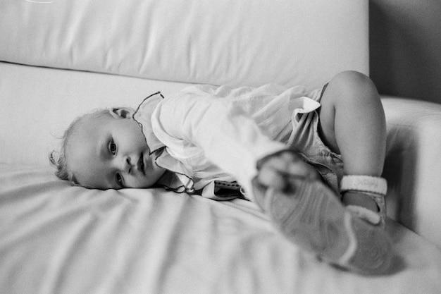 Uma menina, vestida com babados, deitada em um sofá e olhando diretamente para a câmera