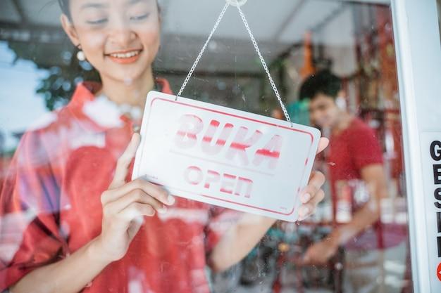 Uma menina vestindo uma camiseta vermelha com uma placa aberta na porta de vidro da frente