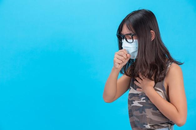 Uma menina vestindo uma máscara mostrando espirros tosse em uma parede azul