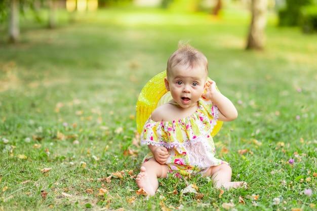 Uma menininha de 7 meses está sentada na grama verde em um vestido e chapéu amarelos e segurando a mão na orelha, caminhando ao ar livre. espaço para texto