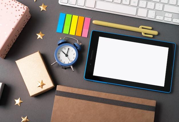 Uma mesa bem decorada com um pequeno relógio, um tablet, teclado, planejador e algumas decorações