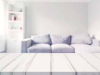 Uma mesa branca vazia na frente do sofá borrão na sala de estar